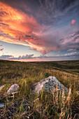 'Clouds Lit At Sunset With Some Glacial Erratics Lying In Grasslands National Park;Saskatchewan Canada'