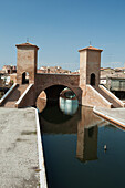 'Italy, Emilia-Romagna, Stone Bridge With Towers And Steps Reflecting In Water; Comacchio'