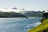The Alaska Marine Highway ferry M/V Tustumena motoring through False Pass at the edge of the Aleutian Islands, Southwest Alaska, summer.