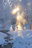 Snowman couple standing next to a stream with sunrays shining through fog and hoar frosted trees in the background, Russian Jack Springs Park, Anchorage, Southcentral Alaska, Winter. Digitally enhanced.