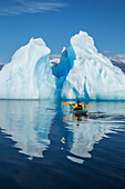 A sea kayaker paddles beside an iceberg in Southeast Alaska's Stephens Passage on a summer evening, Holkham Bay, Tracy Arm. MR_Ed Emswiler, ID#12172012A
