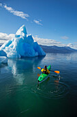 A sea kayaker paddles beside an iceberg in Southeast Alaska's Stephens Passage on a summer evening, Holkham Bay, Tracy Arm. MR_ Ed Emswiler, ID#12172012A