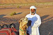 Camel and guide in Liwa desert, Abu Dahbi, United Arab Emirates