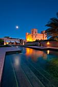 Moon rising above swimming pool and main kasbah of Dar Ahlam Hotel, Skoura, Morocco