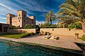 Swimming pool of Dar Ahlam Hotel with main kasbah in background at dawn, Skoura, Morocco