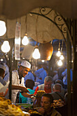 Cook serving food at stall in Djemaa el-Fna Square, Marrakech, Morocco