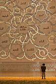 Man praying in front of Qibla wall in Sheikh Zayed Grand Mosque, Abu Dhabi, UAE
