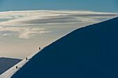 Walkers climbing snowy ridge of Sgorr Dhearg in winter near Glen Coe (Glencoe), Highlands, Scotland, UK