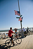 USA, New York State, People and cyclist on boardwalk, Rockaway