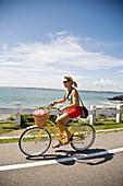 USA, Rhode Island, Young woman bicycling along Ocean Avenue, Newport
