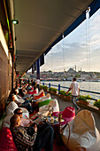 Bars along bottom of Galata Bridge at dusk, Istanbul, Turkey