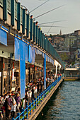 Looking along line of bars and restaurants on Galata Bridge with fishermen above, Istanbul, Turkey