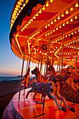 Merry-go-round on Brighton beach at dusk, East Sussex, UK