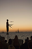 Juggler using lighted torches entertains crowd who have come to watch sunset at Mallory Square, Key West, Florida Keys, USA