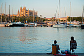 Couple fishing in harbor in front of cathedral at dusk, Palma, Majorca, Spain
