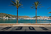 Shadows of letters from Eden Hotel on road in front of beach of Port Soller, Majorca, Spain