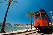 Port Soller to Soller tram going past beach of Port Soller, Majorca, Spain