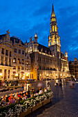 People at restaurant tables at dusk in Grand Place, Brussels, Belgium