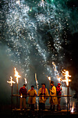People dressed as clergy on stand with fireworks behind them at Newick Bonfire Night, East Sussex, England, UK