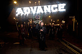 Man dressed as monk carrying 'Advance' banner on Bonfire Night, Lewes, East Sussex, England