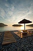 Umbrella and sun loungers on beach opposite Spinalonga Island at dawn, Crete, Greece