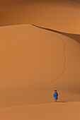 Berber 'Blue man' walking across sand dunes in Erg Chebbi near Merzouga, Sahara Desert, Morocco