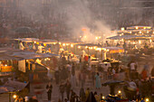 People and food stalls in Djemaa el Fna at dusk, Marrakesh, Morocco