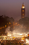 Looking across food stalls in Dejmaa el Fna at dusk with minaret of Koutoubia Mosque behind, Marrakesh, Morocco