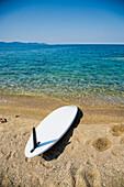 Surfboard and footprints on beach, Ierissos, Halkidiki, Greece