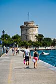 Couple walking towards The White Tower, Thessaloniki, Greece