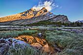 Sunrise Over A Peak Reflected In A Tarn Below Baker Lake In The Skoki Wilderness In Banff National Park, Banff Alberta Canada