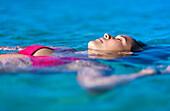 Hawaii, Big Island, Honaunau Bay, Beautiful youn woman floating at oceans surface.