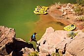 Arizona, Grand Canyon National Park, Man hiking back towrads shored rafts along the Colorado River. EDITORIAL USE ONLY.