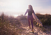 A woman carries her surfboard down a sandy path to the beach, Tarifa cadiz andaulsia spain