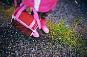 Girl's Matching Pink Boots, Coat And Lunch Box On A Grassy Street