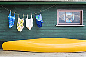 Bathing Suits On Clothes Line With Yellow Canoe Against Cottage, Ontario, Canada