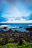 Hawaii, Maui, Hana, Dramatic stormy sunrise over coastline, Rainbow over ocean.