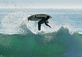 Spain, Andalusia, Cadiz, Male surfer mid air in large splashing wave, Tarifa