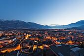 Lights illuminate the buildings at dusk and Lake Maggiore, Locarno, Ticino, Switzerland