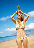 A young woman on the beach in a bikini holding a pineapple on her head, Maui, Hawaii, United States of America