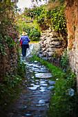 Old Chinese woman walks up winding stone path, Dali City, Yunnan, China