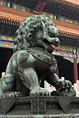 A lion statue in front of a building with colourful ornate facade at Forbidden City, Beijing, China