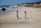 Boy and Girl Running on Sandy Beach
