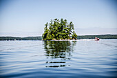 Jet Skier Passing Tree Covered Island Reflecting in Lake Water