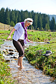 Female hiker refreshing in a stream, Styria, Austria