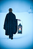 Woman carrying a lantern through snow, Styria, Austria