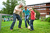 Three generation males playing soccer on playground, Styria, Austria
