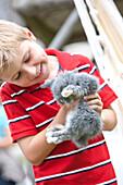 Junge (7 Jahre) hält ein Kaninchen, Steiermark, Österreich