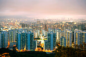 Cityscape with illuminated high-rise buildings in the evening, Hong Kong, China