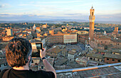 Person taking a photograph of the town hall and the Piazza del Campo from the cathedral museum, Siena, Tuscany, Italy